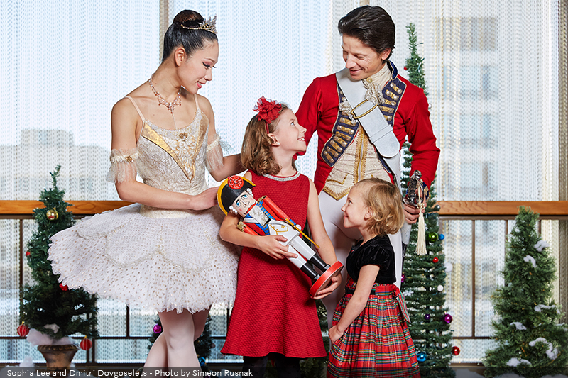 RWB Dancers in costume, standing with children holding a nutcracker