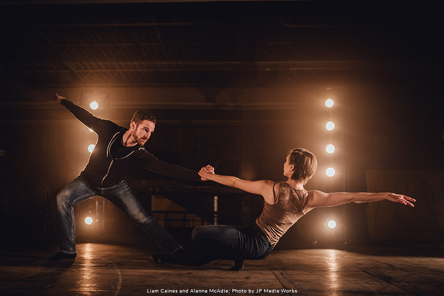 RWB Dancers Liam Caines and Alanna McAdie together in a dance pose, dressed in street clothes against a moody background with stage lights behind them.