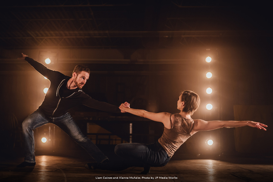RWB Dancers Liam Caines and Alanna McAdie in a dance pose, on a dimly lit stage, in front of stage lights