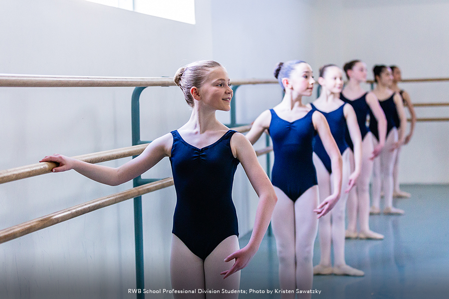 Photo of RWB School Professional Division Students standing in a ballet pose, at the barre, in studio.